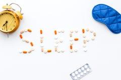 医学帮助得到睡着 好休眠 措辞睡眠标示用安眠药近的睡觉面具和闹钟在白色 免版税库存照片