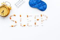 医学帮助得到睡着 好休眠 措辞睡眠标示用安眠药近的睡觉面具和闹钟在白色 免版税库存图片