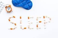 医学帮助得到睡着 好休眠 措辞睡眠标示用安眠药近的睡觉面具和闹钟在白色 库存图片
