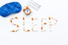 医学帮助得到睡着 好休眠 措辞睡眠标示用安眠药近的睡觉面具和闹钟在白色 库存照片