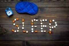 医学帮助得到睡着 好休眠 措辞睡眠标示用安眠药近的睡觉面具和闹钟在黑暗 免版税库存图片