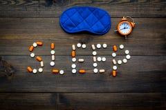 医学帮助得到睡着 好休眠 措辞睡眠标示用安眠药近的睡觉面具和闹钟在黑暗 免版税库存照片