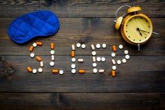 医学帮助得到睡着 好休眠 措辞睡眠标示用安眠药近的睡觉面具和闹钟在黑暗 免版税图库摄影