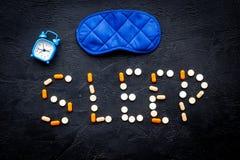 医学帮助得到睡着 好休眠 措辞睡眠标示用安眠药近的睡觉面具和闹钟在黑色 免版税库存图片