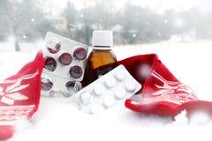 医学用糖浆和红色围巾在雪 库存照片