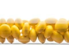 医学黄色药片或片剂在白色背景的棕色玻璃瓶落下 在白色背景的孤立 免版税库存照片