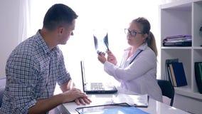 医学,注视着与他的X-射线的医生的沮丧的人在诊所招待会 股票录像