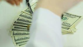 医师在美元放置听诊器 在医学,昂贵的医疗保健的贿赂 股票录像