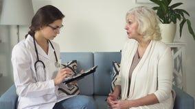 医师谈话与资深妇女在她的房子 股票录像