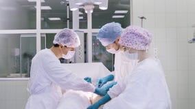 医护人员队制服工作的在耐心执行的操作在现代手术室 影视素材