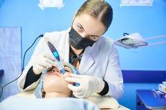 医治在一件白色外套,并且在面孔的黑面具做ultrason 图库摄影