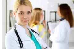 医治站立在有她的同事的一个医院办公室的妇女或护士在背景中 关心眼睛医疗保健卫生学医学 免版税库存照片