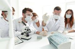 医生与试管和显微镜一起使用在实验室 图库摄影