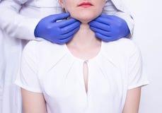 医生专家诊断在白种人女孩的喉头的触诊扩大的淋巴结出现的和 免版税库存照片