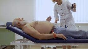 医生为心电图学的工具为老人做准备 股票录像