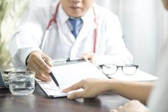 医生介绍签字在病历的患者在trea前 免版税库存图片