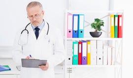 医生写某事并且在办公室站立 免版税库存照片
