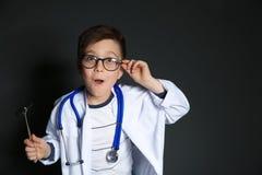 医生制服的逗人喜爱的小孩有反射锤子的 库存照片