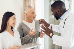 医生告诉护士一名年长男性患者怎样应该采取药片 库存图片