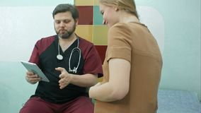 医生和孕妇一起看数字式片剂 免版税图库摄影