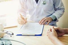 医生和患者与关于medicatio的患者坐并且谈话 库存照片