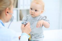 医生和患者在医院 小女孩由有听诊器的儿科医生审查 关心健康医学 免版税库存照片