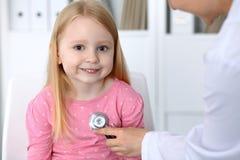医生和患者在医院 有听诊器的医师被审查的孩子 图库摄影
