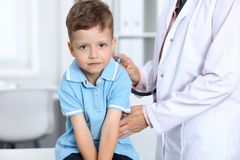 医生和患者在医院 获得愉快的小男孩乐趣,当被审查与听诊器时 医疗保健和 免版税库存图片