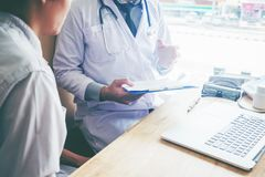 医生和患者坐并且谈话 在窗口附近的桌上 库存照片