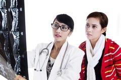 医生和患者查阅X-射线结果 图库摄影