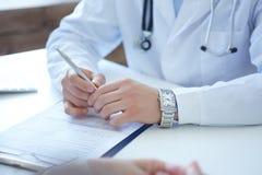 医生和患者谈论某事,手在桌上 医疗保健和医疗概念 图库摄影