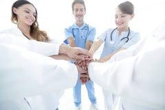 医生和护士堆积手的一个医疗队的 库存图片