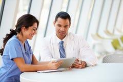 医生和护士开非正式会议在医院军用餐具 免版税库存照片