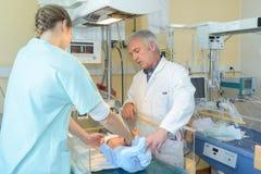 医生和护士有新出生的婴孩的 免版税库存图片