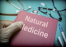 医生在一个医学实验室支持自然医学书  免版税库存照片