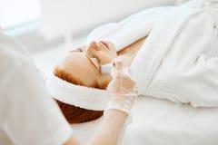 医生在做激光治疗前应用在妇女的与氢结合的胶凝体面具 免版税库存照片
