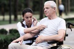 医生在夏天公园审查有一个听诊器的一名年长患者 库存图片