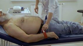 医生在年长人的手上把电极放在心电图学前 股票视频