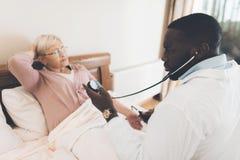 医生在老人院审查一名年长患者 免版税库存图片