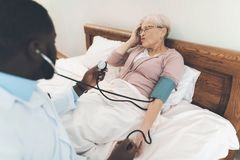 医生在老人院审查一名年长患者 库存图片