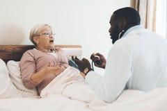 医生在老人院审查一名年长患者 免版税库存照片