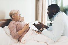 医生在老人院审查一名年长患者 免版税图库摄影