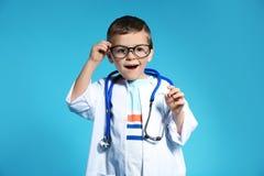 医生外套的逗人喜爱的孩子有听诊器的 免版税图库摄影