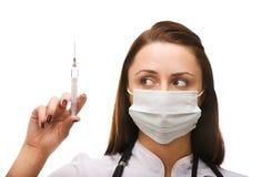 医生女性查找的注射器年轻人 免版税库存照片