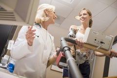 医生女性监控患者踏车 免版税库存照片