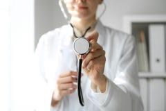 医生妇女在工作 使用听诊器的女性医师画象  r 库存图片