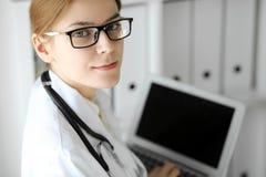 医生妇女在工作 使用膝上型计算机的女性医师画象在医院办公室 医学和医疗保健概念 免版税图库摄影