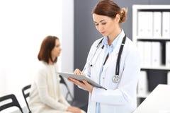 医生妇女在工作 填装医疗形式的女性医师画象,当站立近的总台在诊所时 库存照片
