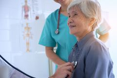 医生审查使用听诊器的资深患者 免版税库存照片