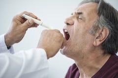 医生审查喉咙痛的老人 免版税库存图片
